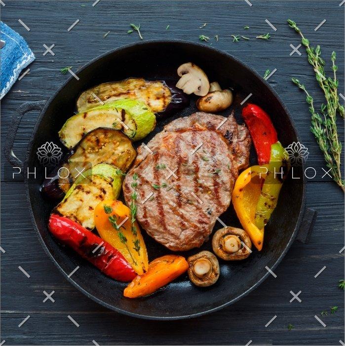 grilled-beef-steak-on-dark-wooden-table-P4NLM25